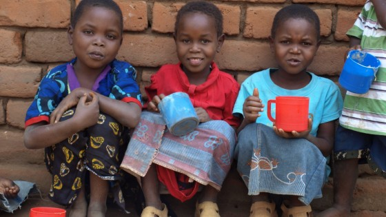 Malawi - feeding 3 girls - 3 girls with cups of food